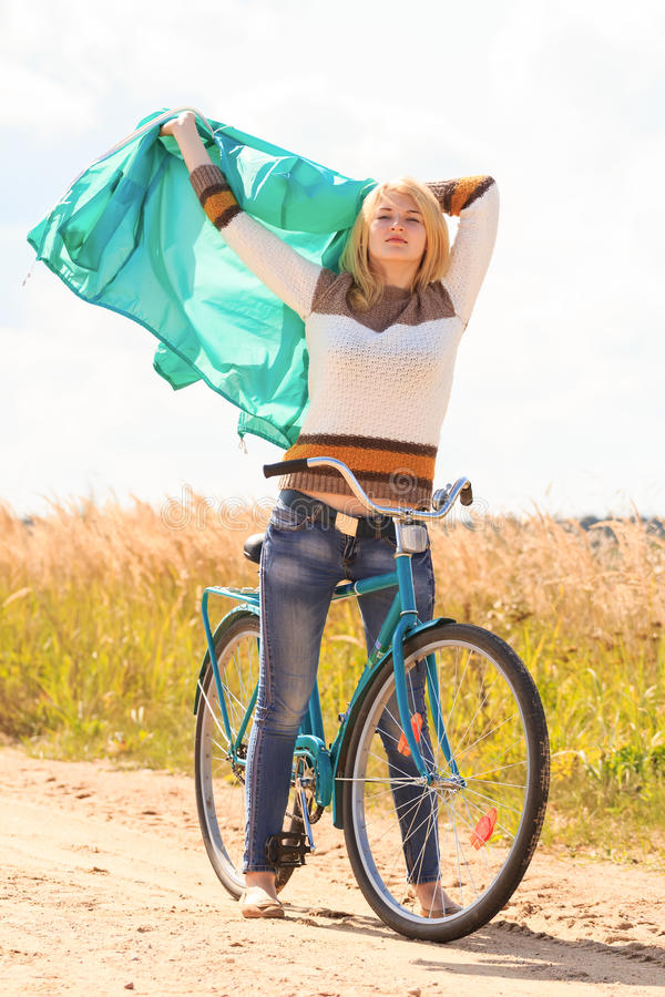 Happy blonde girl at cycling on dirt road royalty free stock photography