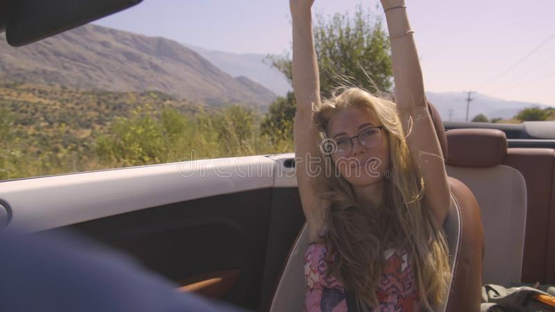 Woman in Cabriolet. Happy blonde girl relaxing enjoying sunshine sitting in convertible car. Road trip vacation, driving away on travel. Freedom concept, woman royalty free stock image