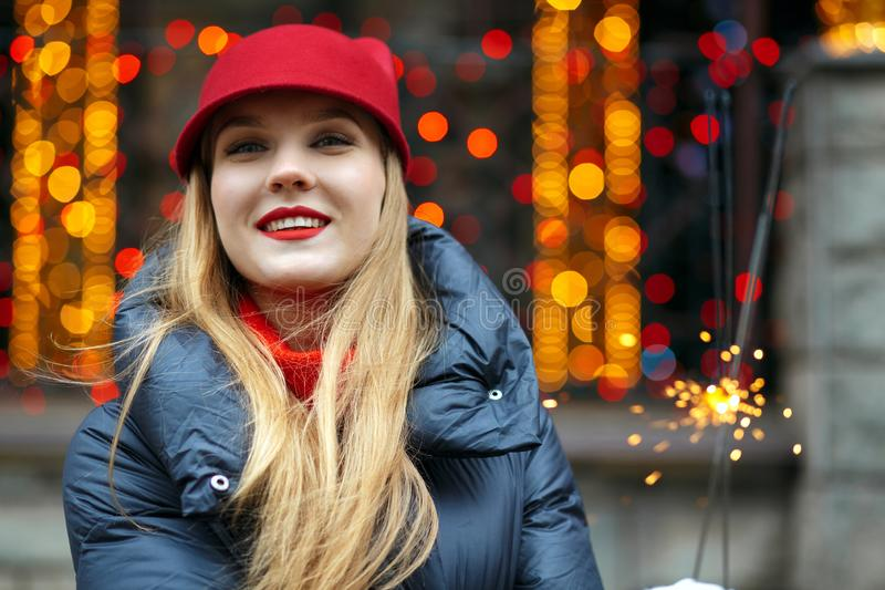 Happy blonde girl wearing winter outfit celebrating winter holigdays with a sparklers. Space for text royalty free stock image