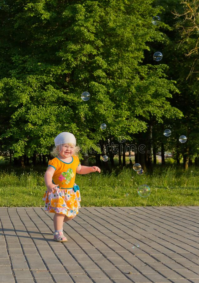 Happy blonde little girl in the summer having fun with soap bubbles outdoors stock images