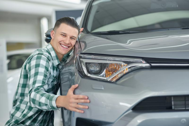 Happy blonde man smiling after buying his first car. Attractive young client choosing auto and squatting near it. Handsome owner in checkered shirt really stock photos