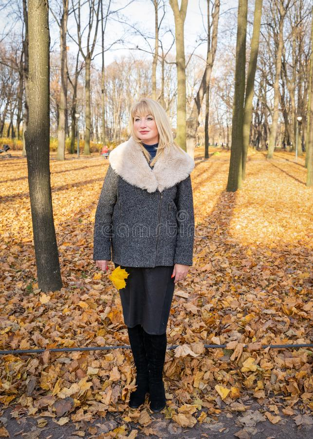 Happy blonde mature woman is standing in autumn park and thinking. Beautiful woman is relaxing in nature on sunny day. Portrait of stock images