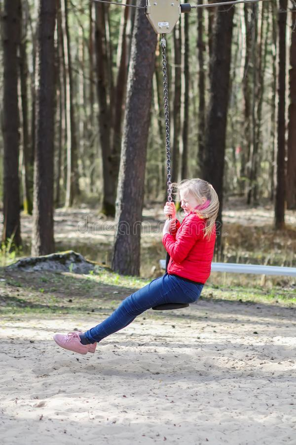 Happy blonde teenager girl dressed in red jacket and blue jeans jumping and riding down with bungee in children`s playground in wa. Happy blonde teenager girl royalty free stock images