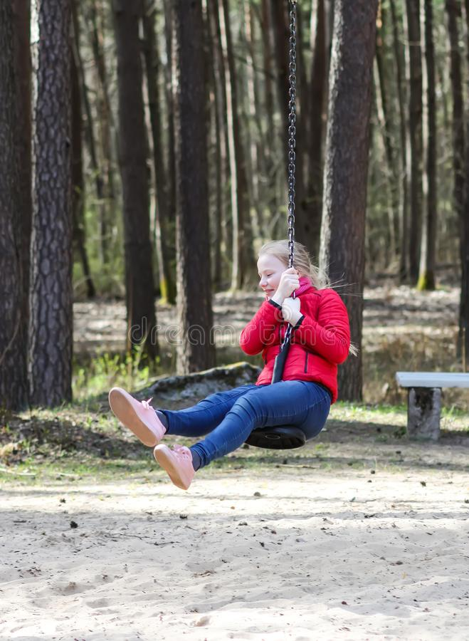 Happy blonde teenager girl dressed in red jacket and blue jeans jumping and riding down with bungee in children`s playground in wa. Happy blonde teenager girl stock images