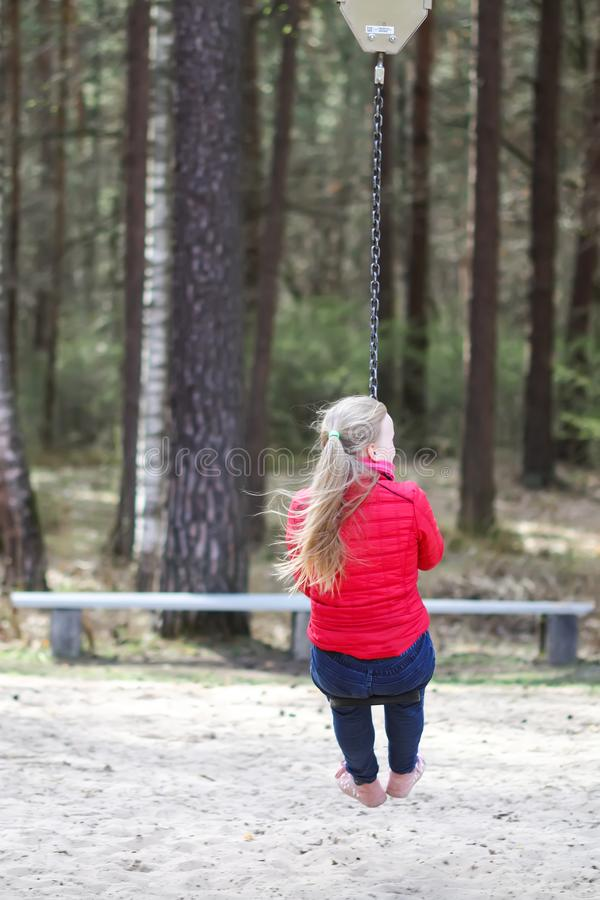 Happy teenager girl jumping with bungee in park. Happy blonde teenager girl jumping with bungee in park royalty free stock photography
