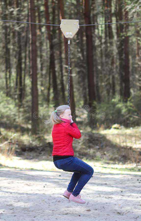 Happy teenager girl jumping with bungee in park. Happy blonde teenager girl jumping with bungee in park royalty free stock image