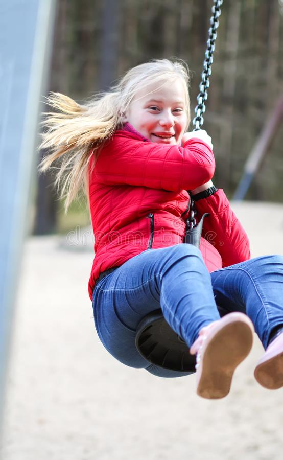 Happy teenager girl jumping with bungee in park. Happy blonde teenager girl jumping with bungee in park stock images