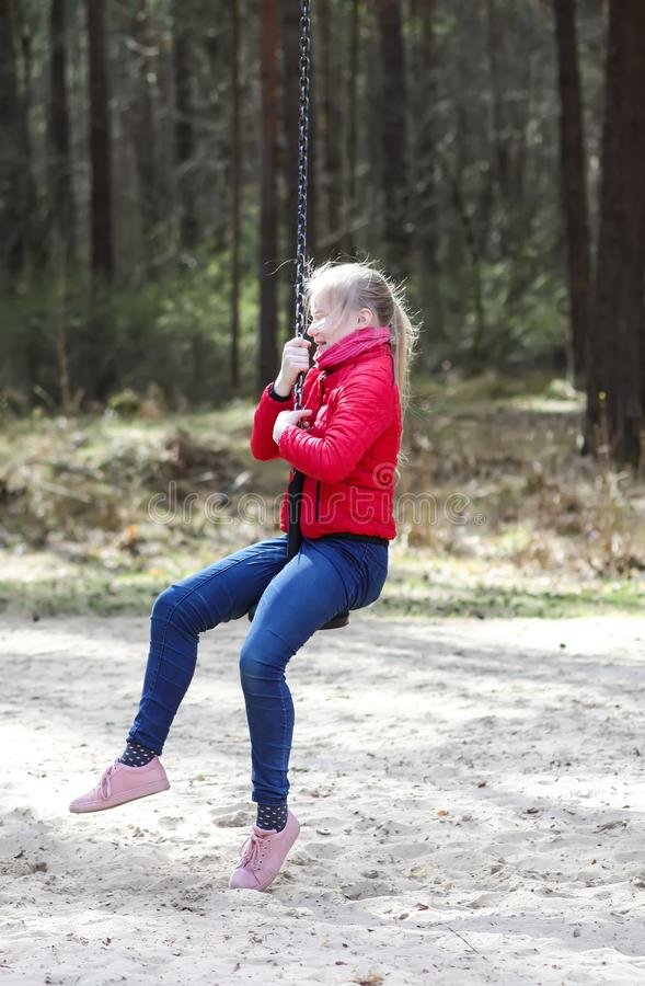 Happy teenager girl jumping with bungee in park. Happy blonde teenager girl jumping with bungee in park royalty free stock photo