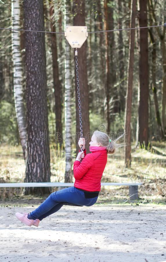 Happy blonde teenager girl jumping with bungee in park. Happy blonde teenager girl dressed in red jacket and blue jeans jumping and riding down with bungee in stock photo