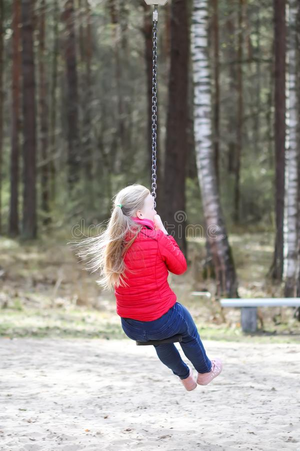Happy blonde teenager girl dressed in red jacket and blue jeans jumping and riding down with bungee in children`s playground in wa. Happy blonde teenager girl stock image