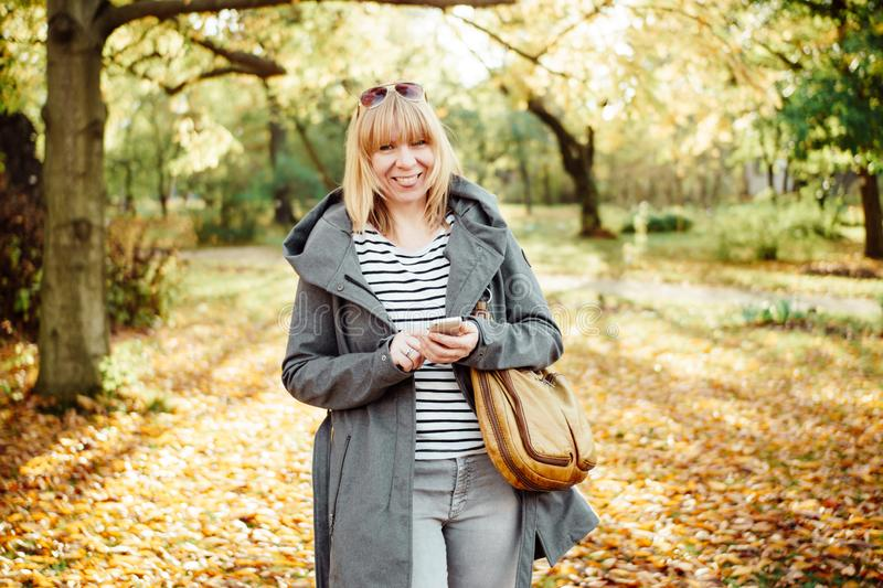 Happy blonde woman in a autumnal forest or park texting with her mobile phone. Communication, technology and outdoors concept royalty free stock images