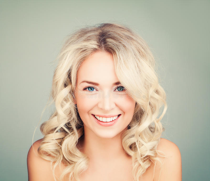 Happy Blonde Woman with Blonde Curly Hair. Smiling Fashion Model with Wavy Hairstyle royalty free stock images