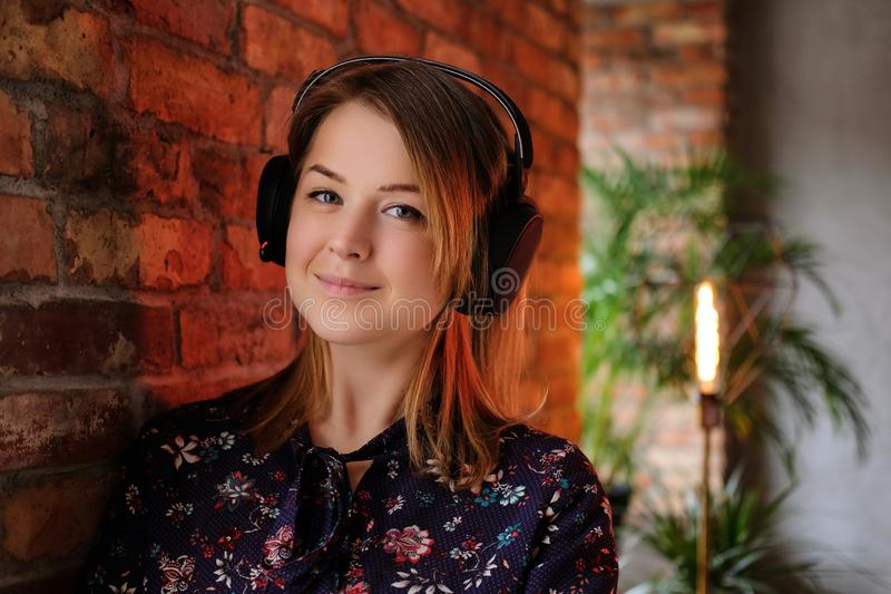 Happy blonde woman in dress listening to music in headphones while leaning on a brick wall in room with loft interior. stock photography