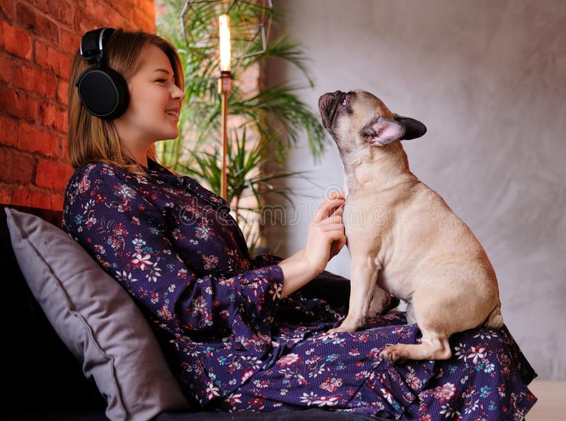 Happy blonde woman in dress playing with her cute pug and listening to music in room with loft interior. royalty free stock photography