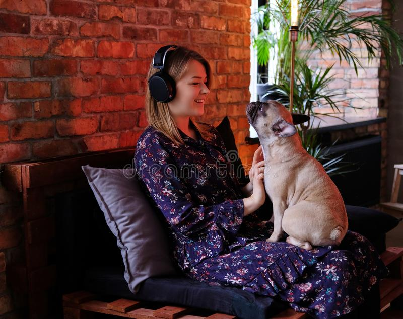 Happy blonde woman in dress playing with her cute pug and listening to music in room with loft interior. royalty free stock image
