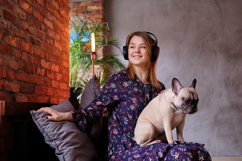 Happy blonde woman in dress sitting with her cute pug on a handmade sofa and listening to music in a room with loft royalty free stock photography