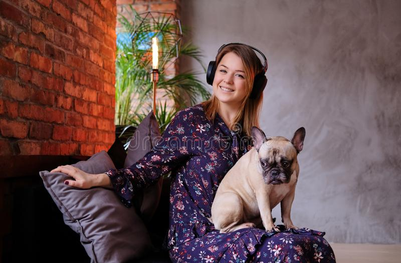 Happy blonde woman in dress sitting with her cute pug on a handmade sofa and listening to music in a room with loft royalty free stock images