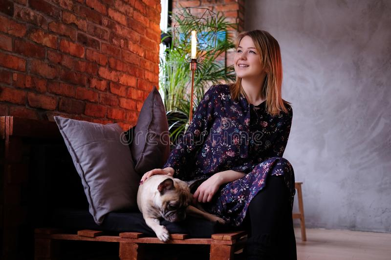 Happy blonde woman in dress sitting with her cute pug on a handmade sofa in room with loft interior. royalty free stock image