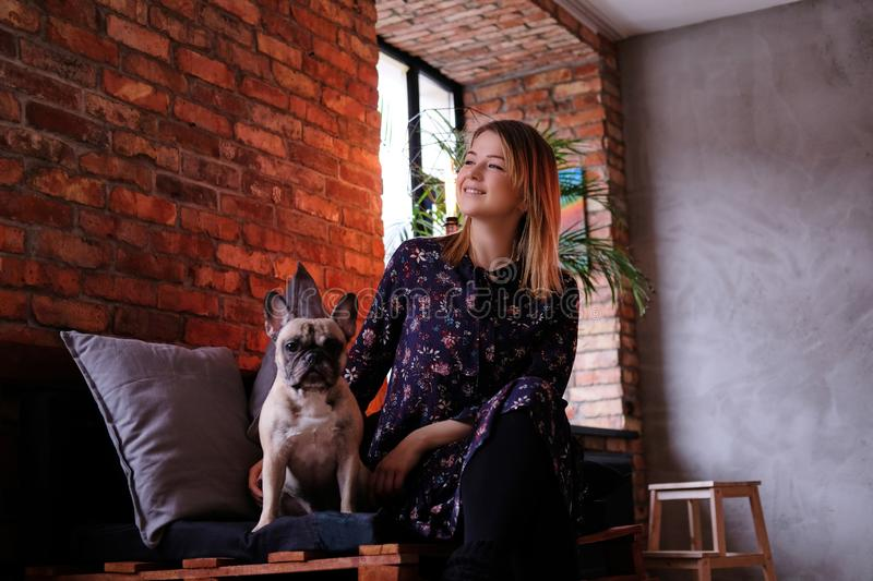 Happy blonde woman in dress sitting with her cute pug on a handmade sofa in room with loft interior. royalty free stock images