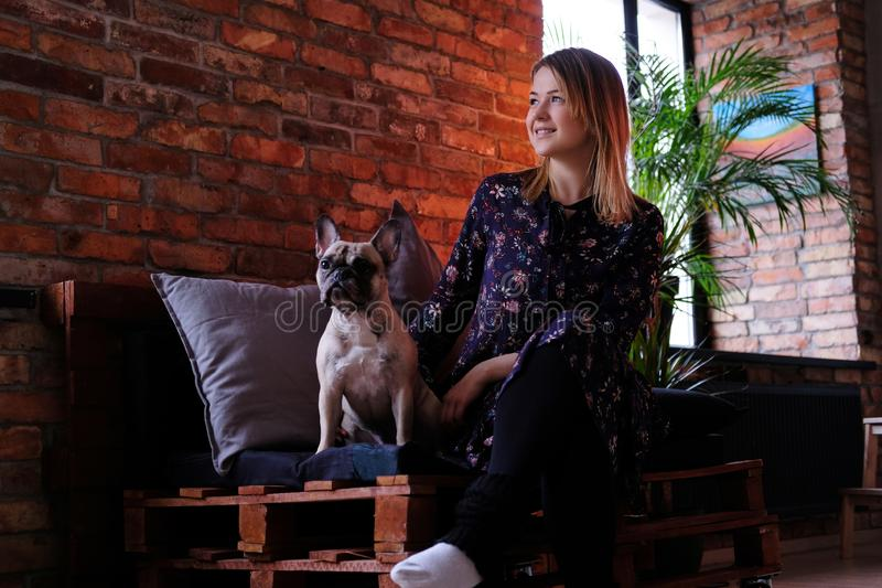 Happy blonde woman in dress sitting with her cute pug on a handmade sofa in room with loft interior. stock photos