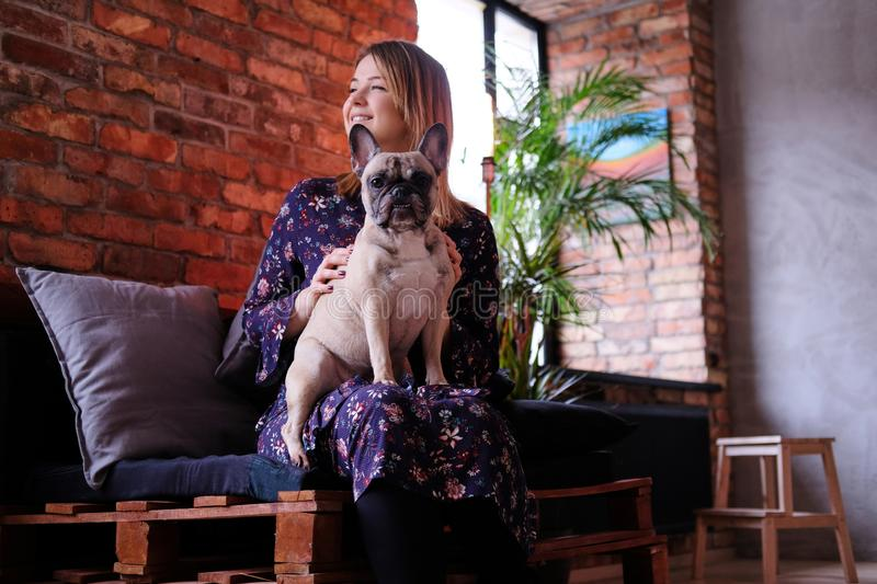 Happy blonde woman in dress sitting with her cute pug on a handmade sofa in room with loft interior. stock photo