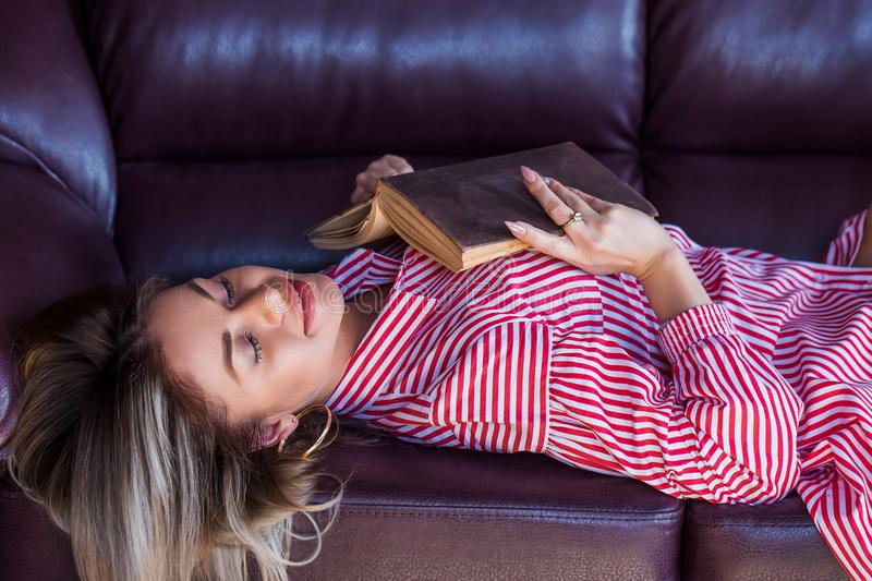 A happy blonde woman is lying on the couch and reading a good book, with her eyes closed dreaming about something and smiling royalty free stock photos