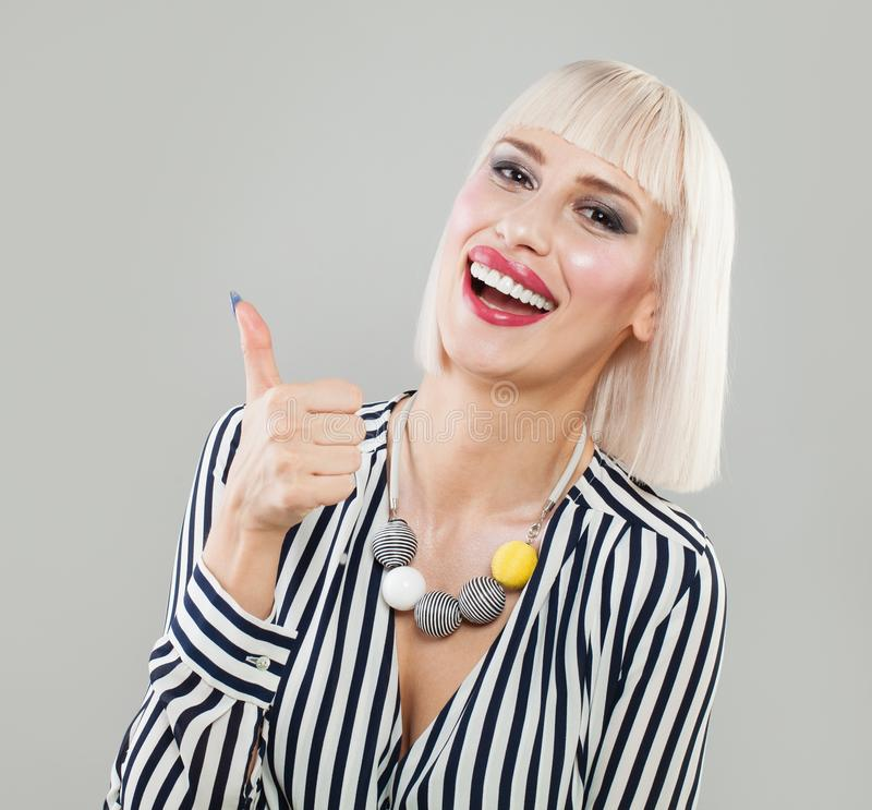 Happy blonde woman showing thumbs up. royalty free stock photos