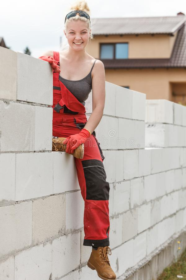 Woman in dungarees working on construction site royalty free stock photos