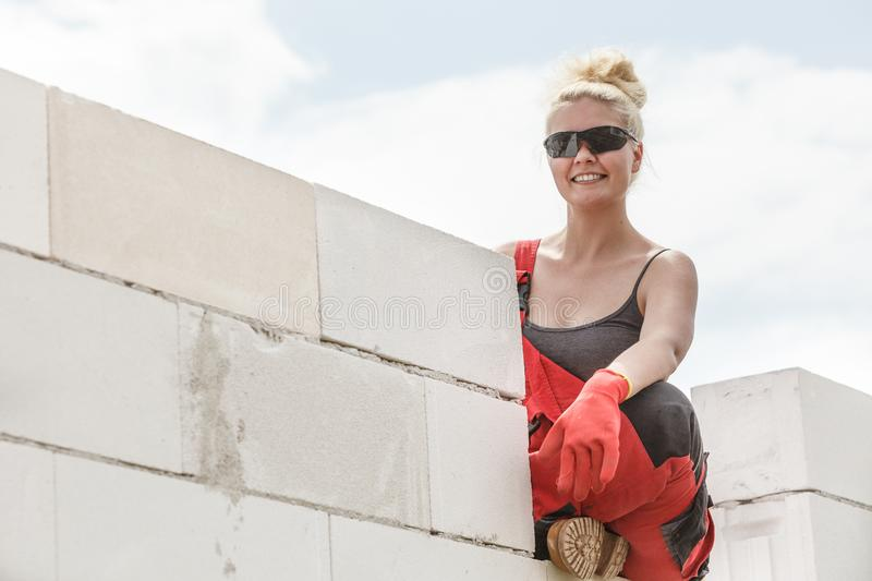 Woman in dungarees working on construction site stock image