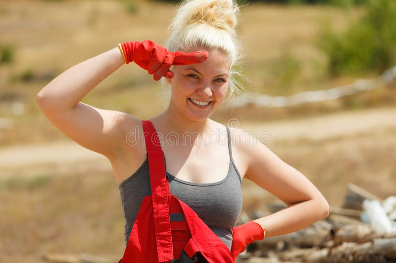 Woman in dungarees working on construction site royalty free stock photo