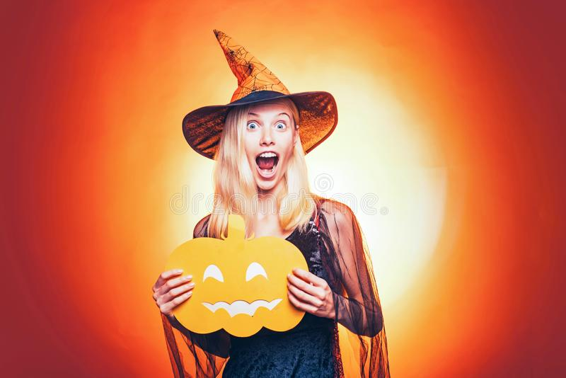 Happy blonde woman in witch halloween costume with hat standing and smiling over white background. Halloween Witch with stock photography