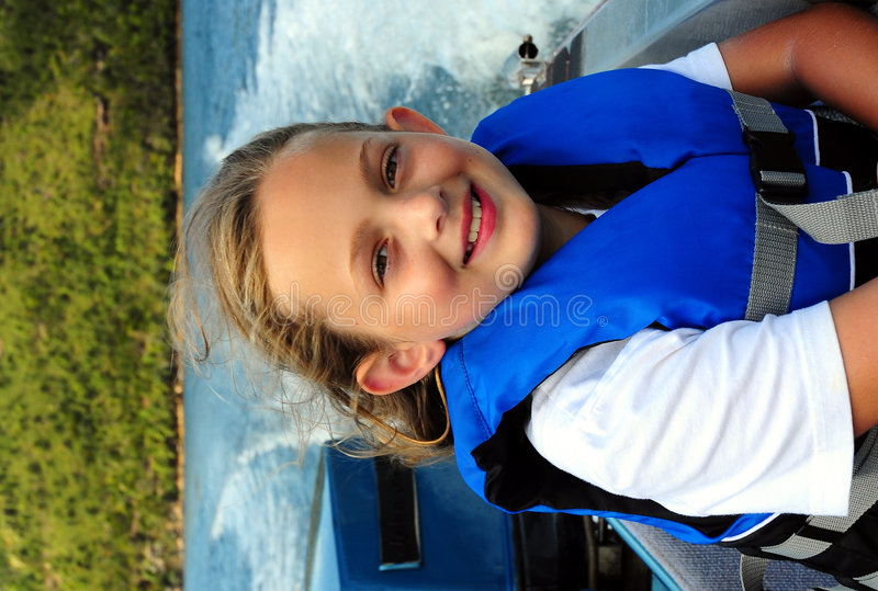 Happy on a boat. Girl happy on a boat with life vest royalty free stock photography