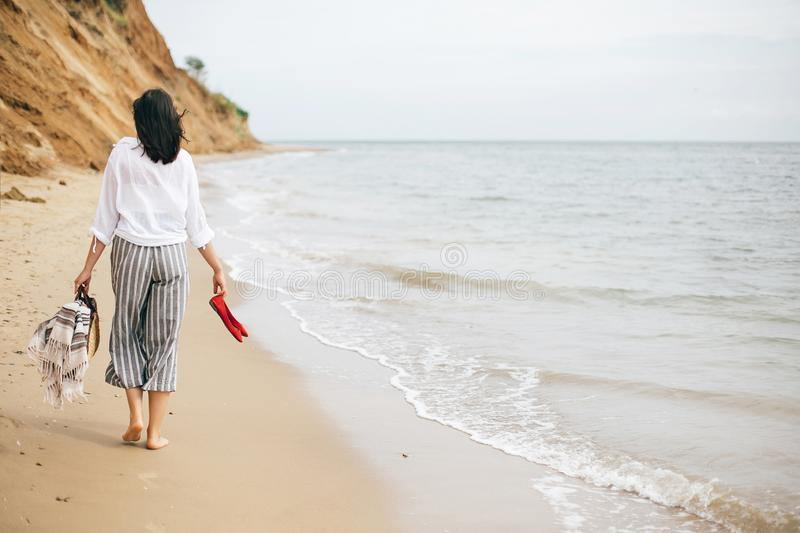 Happy boho woman relaxing at sea, enjoying walk on tropical island. Stylish hipster girl walking barefoot on beach, holding bag. And shoes in hand. Summer royalty free stock image