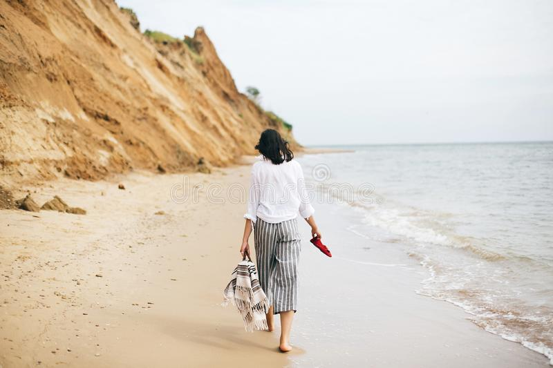 Happy boho woman relaxing at sea, enjoying walk on tropical island. Stylish hipster girl walking barefoot on beach, holding bag. And shoes in hand. Summer stock images