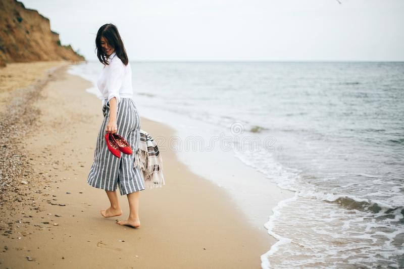 Happy boho woman relaxing at sea, enjoying walk on tropical island. Stylish hipster girl walking barefoot and smiling on beach,. Holding bag and shoes in hand royalty free stock photography