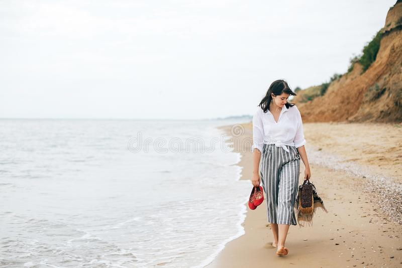 Happy boho woman relaxing at sea, enjoying walk on tropical island. Stylish hipster girl walking barefoot and smiling on beach,. Holding bag and shoes in hand stock photo