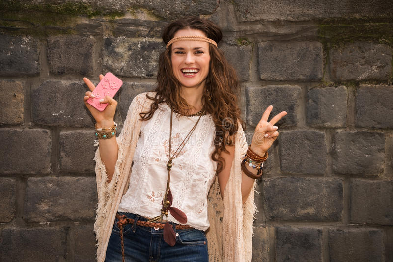 Happy boho young woman near stone wall showing victory gesture. Longhaired hippy-looking young lady in jeans shorts, knitted shawl and white blouse standing near stock images