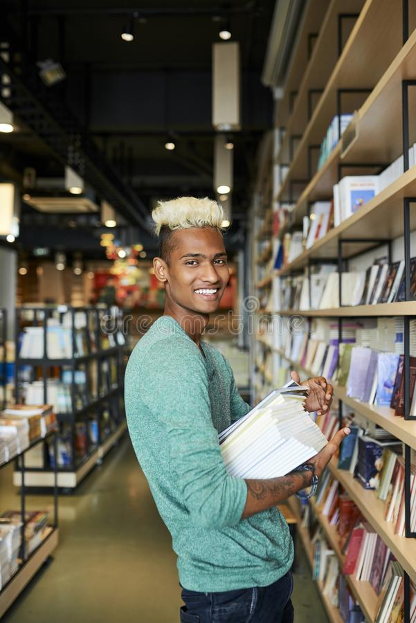 Happy bookstore employee in shop. Happy handsome young black bookstore employee with blond Mohawk standing in modern shop and holding stack of books while stock photography