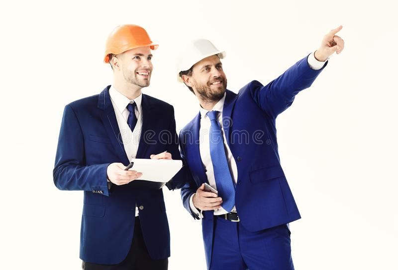 Happy boss pointing something to employee. Businessman and building surveyor with smiling and cheerful faces. Site royalty free stock images