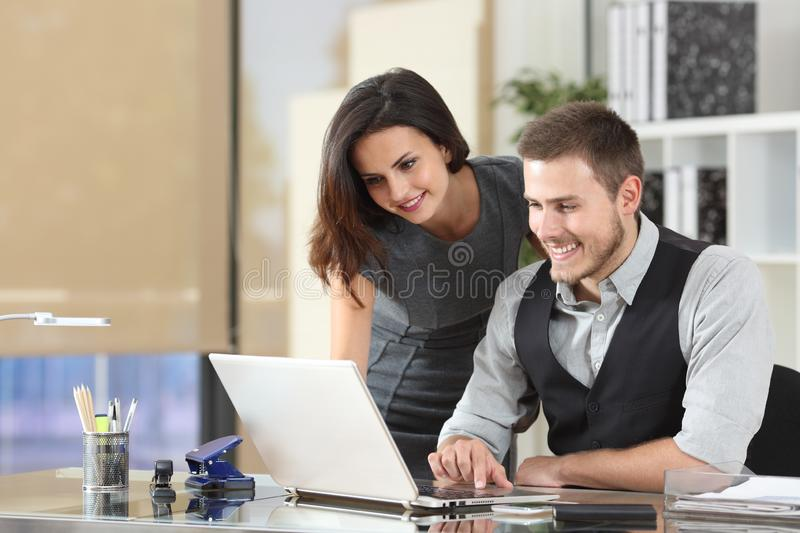 Happy boss teaching intern at office stock images