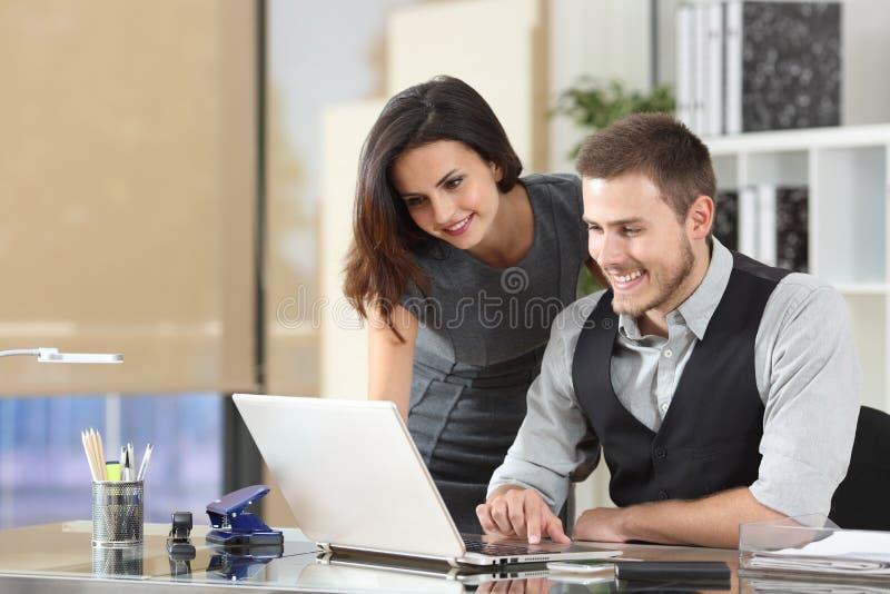 Happy boss teaching intern at office. Happy boss teaching intern using a laptop at office stock images