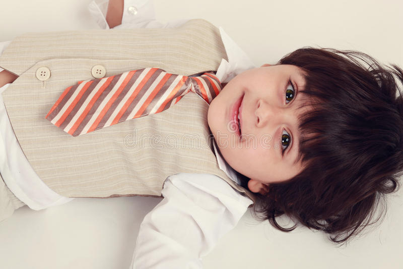 Happy boy. Happy toddler wearin a suit with flower bokeh in the background royalty free stock photos
