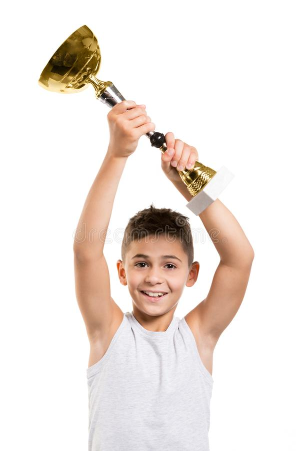 Happy boy athlete raised golden sports cup over his head, winner in a contest, concept, on a white background royalty free stock image