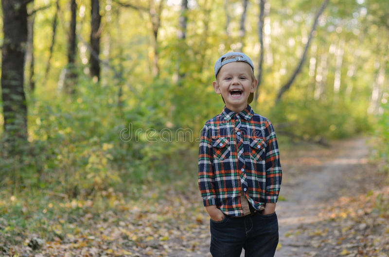 Happy boy in autumn forest stock image