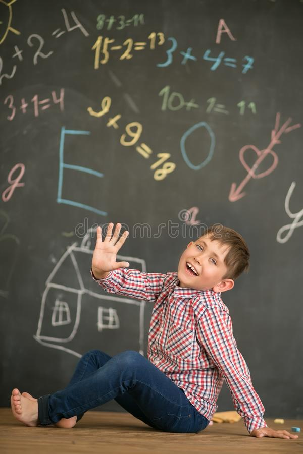 Happy boy on the background of a school board showing five fingers stock photography