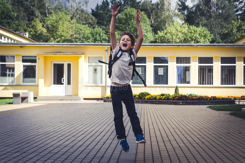 Happy boy with backpack jumping and having fun in front of school . Back to School education concept. stock photography
