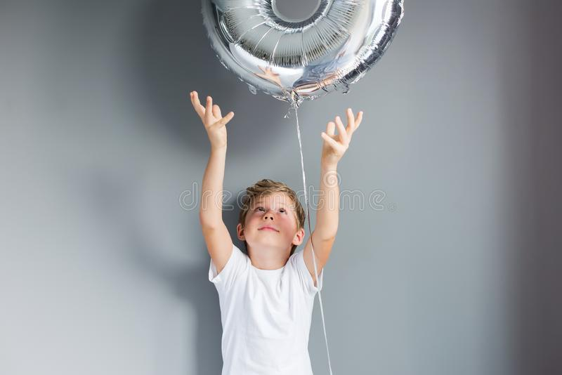 Happy boy ballon number 8 birthday gray wall. Happy boy with ballon number 8 on his birthday on gray wall. Happy childhood celebration concept stock photography