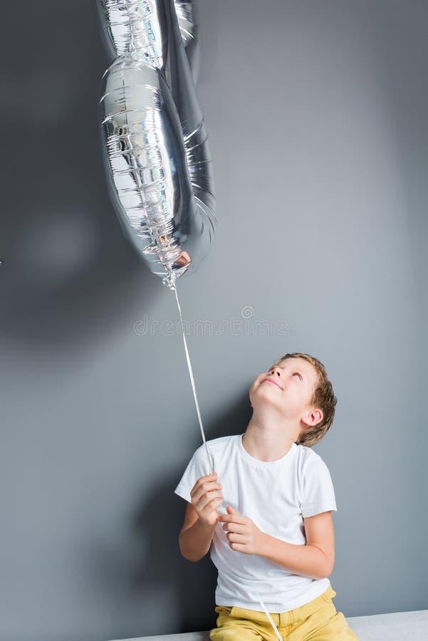 Happy boy ballon number 8 birthday gray wall. Happy boy with ballon number 8 on his birthday on gray wall. Happy childhood celebration concept royalty free stock image