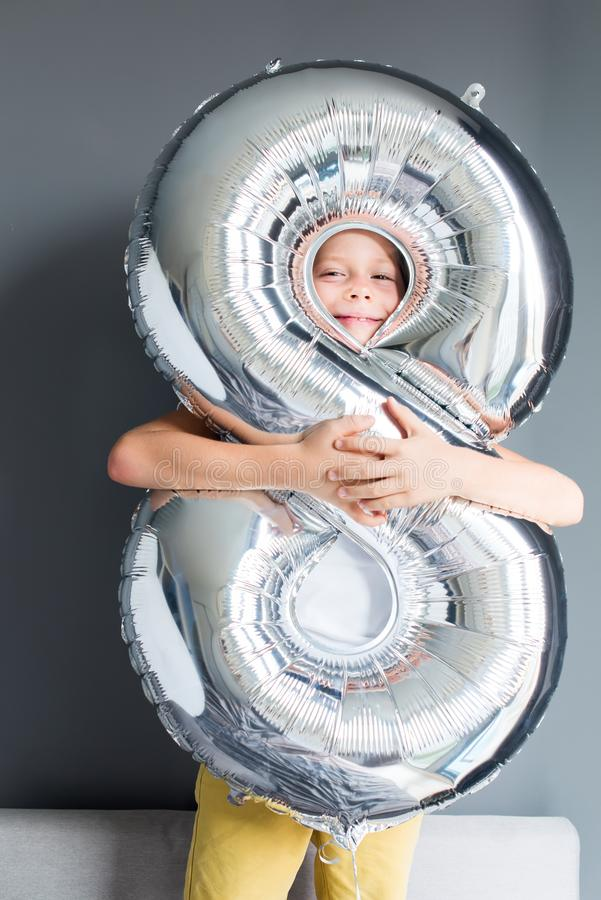 Happy boy ballon number 8 birthday gray wall. Happy boy with ballon number 8 on his birthday on gray wall. Happy childhood celebration concept royalty free stock photo