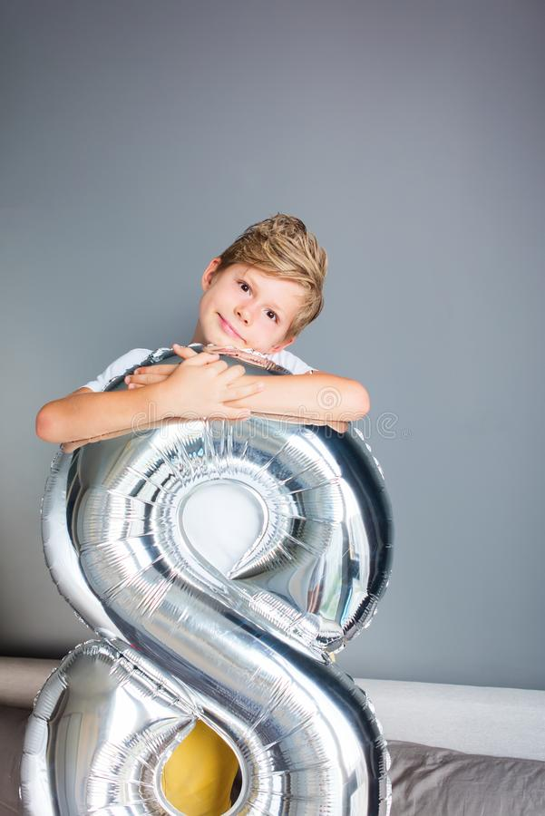 Happy boy ballon number 8 birthday gray wall. Happy boy with ballon number 8 on his birthday on gray wall. Happy childhood celebration concept royalty free stock photography